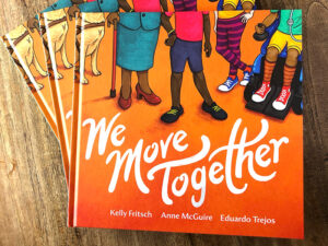 Stack of We Move Together books on a wooden table